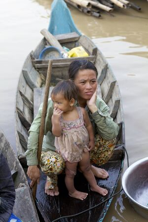 Tonle Sap Lake, Cambodia - April 1: Unidentified mother and child in wooden boat floating in Tonle Sap Lake, Cambodia on April 1, 2011.