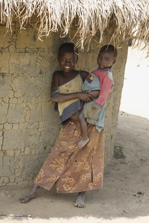ugandan: LIRA, UGANDA - JUNE 9: An unidentified girl holds her baby brother under thatched roof of their hut in Lira, Uganda on June 9, 2007. UNHCR estimates there to be over 136,000 refugees in Uganda.