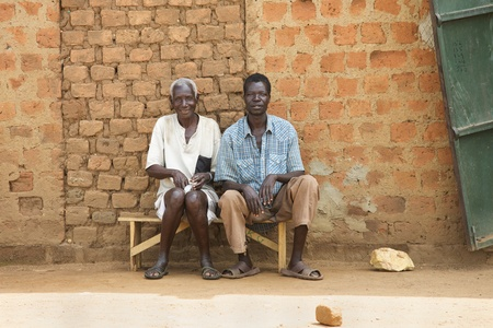 ugandan: LIRA, UGANDA - JUNE 9: Two villagers wait on bus bench in Lira, Uganda on June 9, 2007.  Editorial