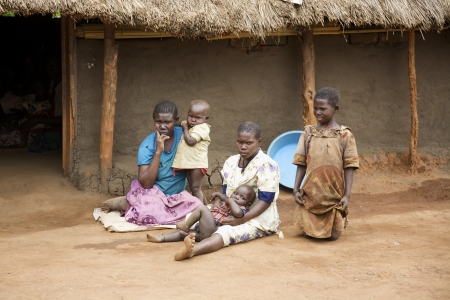 Lira, Uganda - June 9, 2007: A family outside their thatched roof hut in Lira, Uganda on June 9, 2007
