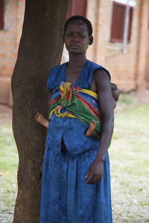 uganda: Lira, Uganda - June 9, 2007: A mother with her baby wrapped around waste in Lira, Uganda on June 9, 2007