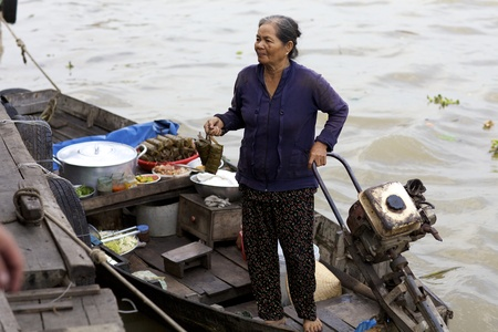 Can Tho, Vietnam - Jan 7: Unidentified Vietnamese woman selling fresh cooked food from boat at the famous Can Tho Floating Market in Can Tho, Vietnam on January 7, 2012