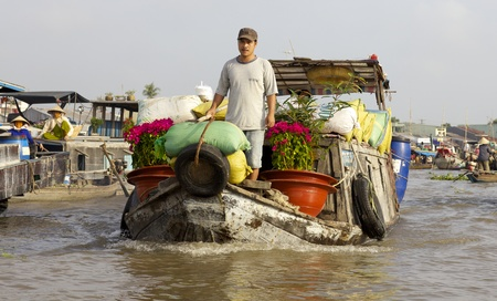 can tho: Can Tho, Vietnam - Jan 7: Unidentified Vietnamese selling flowers from their boat at the famous Can Tho Floating Market in Can Tho, Vietnam on January 7, 2012