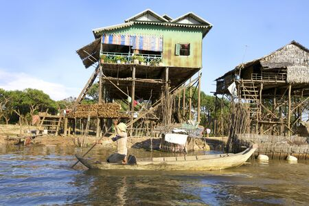 above 21: Tonle Sap Lake, Cambodia - Jan 21: Typical Cambodian houses built on stilts above water level in Tonle Sap Lake, Cambodia on January 21, 2012