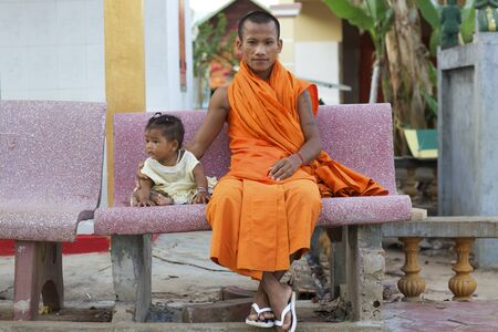 Siem Reap, Cambodia - Jan 21, 2012: A Cambodian monk sits on broken bench with baby next to him in Siem Reap, Cambodia on January 21, 2012.