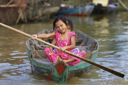 Siem Reap, Cambodja - 23 januari 2012: Twee Cambodjaanse kinderen roeien hun boot op Tonle Sap meer in Siem Reap, Cambodja op 23 januari 2012. Redactioneel