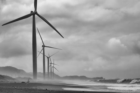 Wind Turbine Farm op Ocean Beach in Bangui Bay, Filippijnen op Stormachtige Dag Stockfoto