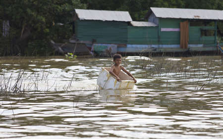 Siem Reap, Cambodia - Jan 23, 2012: Unidentified Cambodian child floats across water in styrofoam ice chest on Tonle Sap Lake in Siem Reap, Cambodia on January 23, 2012.