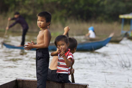 Siem Reap, Cambodia - Jan 23, 2012: Three Cambodian children row their boat on Tonle Sap Lake in Siem Reap, Cambodia on January 23, 2012. 報道画像