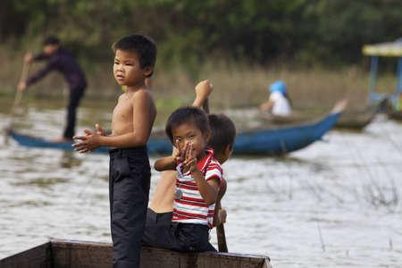 Siem Reap, Cambodia - Jan 23, 2012: Three Cambodian children row their boat on Tonle Sap Lake in Siem Reap, Cambodia on January 23, 2012. Редакционное