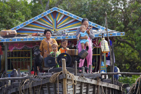 SIEM REAP, CAMBODIA-JAN 23: Cambodian family on their floating home on Tonle Sap Lake in Siem Reap, Cambodia on January 23,2012.  Stock Photo - 12339547