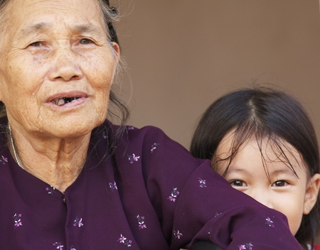 DUONG LAM, VIETNAM- SEPT 3: An unidentified Vietnamese child sits with her grandmother on September 3, 2010 in Duong Lam Village, Vietnam.  Stock Photo - 13576045