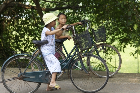 Duong Lam Village, Vietnam- Sept 3: Unidentified Vietnamese children riding bikes in Duong Lam Village, Vietnam on September 3, 2010.