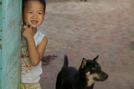 Duong Lam 村、ベトナム - 9 月 3日: ベトナムの少年はドアの後ろから 2010 年 9 月 3 日に Duong Lam 村、ベトナム。古代の村、ハノイの西 60 km 1,400 年前にさ 報道画像
