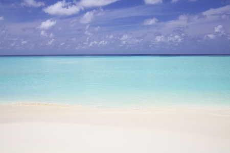 Blue ocean water with sand beach photo