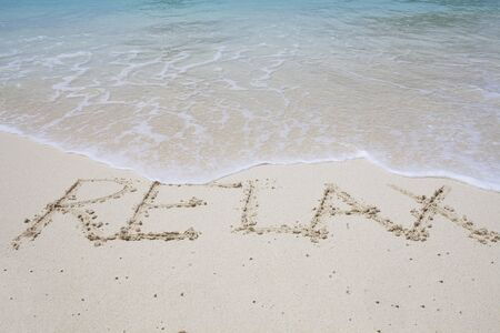 Relax written into sand beach with blue ocean water wave above photo