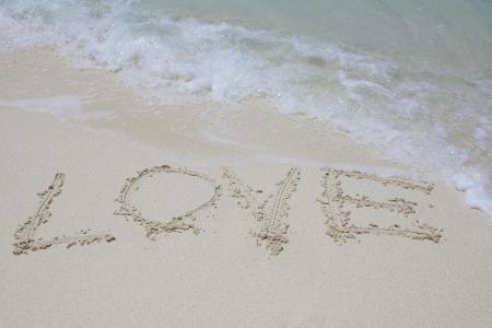 Love written into sand on beach photo