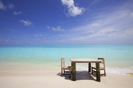 Table and chairs on white sand ocean beach Stock Photo