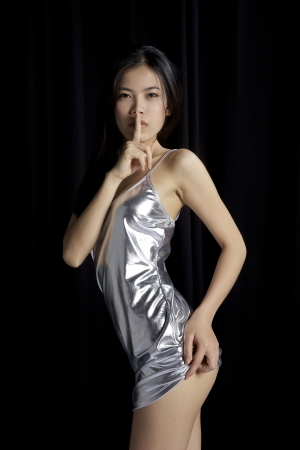 quiet adult: Asian girl showing silence with finger Stock Photo