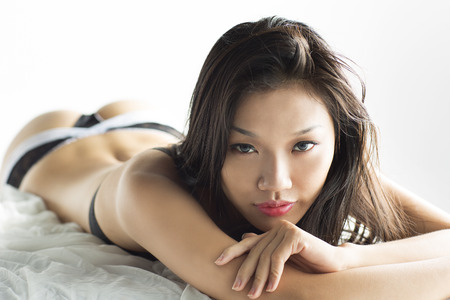 Beautiful Asian Girl laying on bed photo