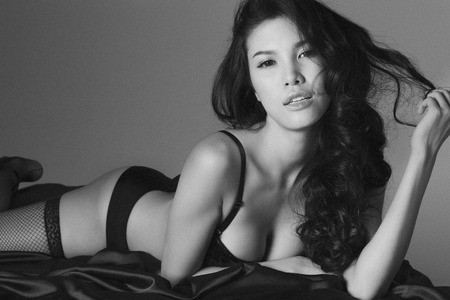 Beautiful asian girl in sexy lingerie posing on bed monochrome photo