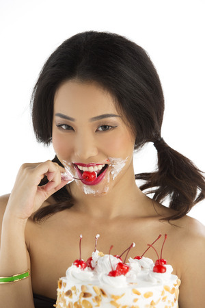 Asian girl eating cherry from Birthday cak photo