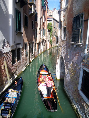 punting: Gondolier punting gondola in along narrow Venetian canal