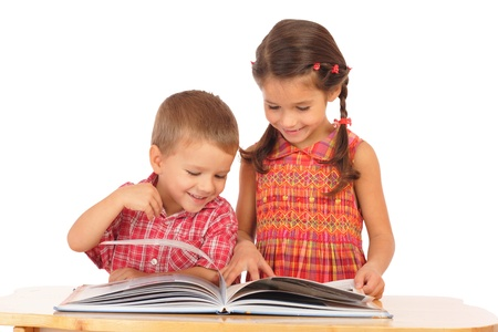 Two smiling children reading the book on the desk Stock Photo