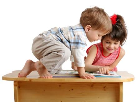 bambini che leggono: Due sorridente bambini giocare leggendo il libro sulla scrivania Archivio Fotografico