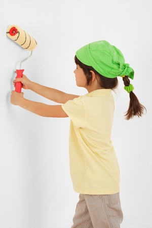 paintroller: Little girl with paintroller in hands near white wall