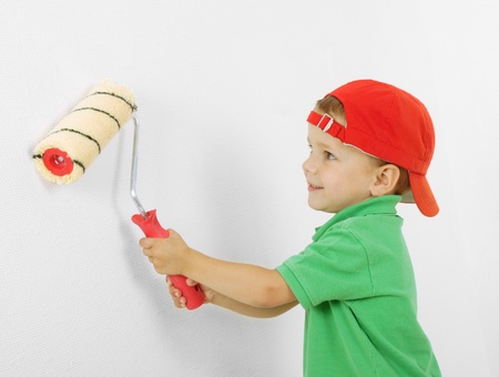 paintroller: Little boy with paintroller in hands near white wall