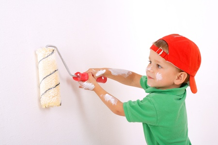 Little worker with paintroller on white wall