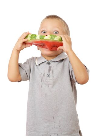 Little boy eating watermelon with drops of juice on shirt, studio shoot photo
