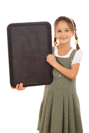 Little schoolgirl with empty vertical chalkboard, isolated on white photo