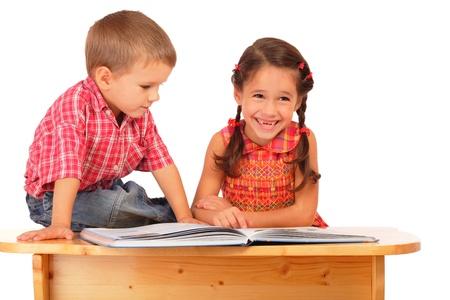 ni�os leyendo: Dos ni�os sonrientes leyendo el libro sobre la mesa, aislado en blanco