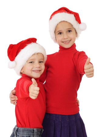Smiling little children in Christmas hats and thumbs up sign, isolated on white photo