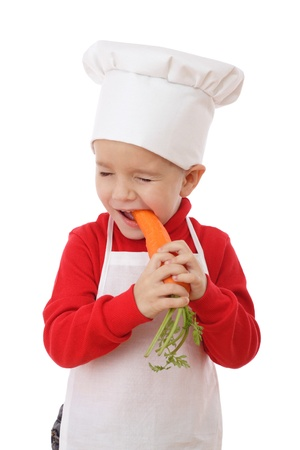 Little chief-cook tasting the carrot, isolated on white Stock Photo - 9344082