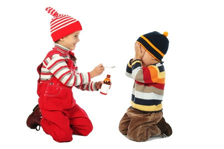 Little boy and smiling girl with spoon and bottle of medicine Stock Photo - 9344065