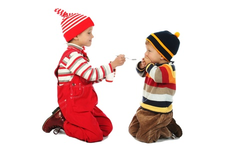 Little boy and smiling girl with spoon and bottle of medicine photo