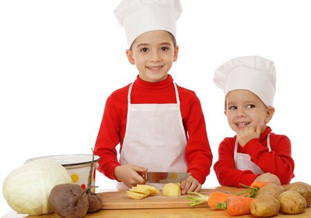 niños cocinando: Sonriente poco jefe-cocinas en el escritorio con verduras, aislados en blanco