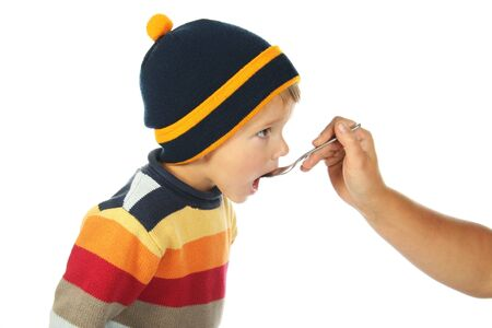 cough medicine: little open-mouthed boy in the sweater with spoon held by the adult persons hand