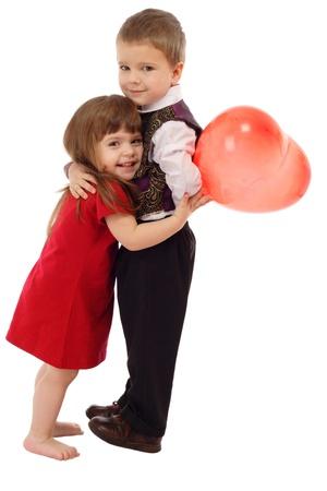 tenderly: Little boy abbracciarsi bambina con palloncino rosso, isolata on white Archivio Fotografico