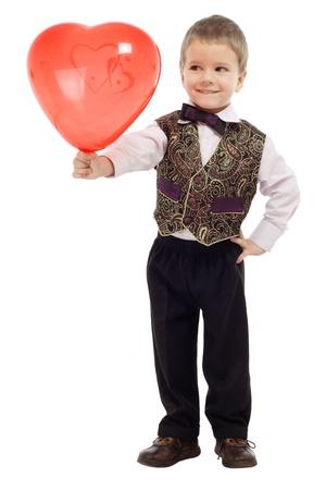 d?a: Ni�o sonriente da un globo rojo, aislado en blanco Foto de archivo