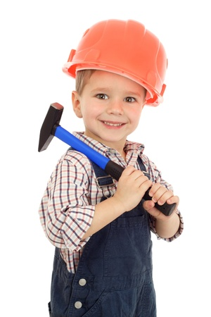 Little smiling builder in coveralls and helmet with hammer, isolated on white photo