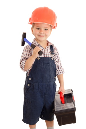 Little smiling builder in coveralls and helmet with hammer and toolbox, isolated on white