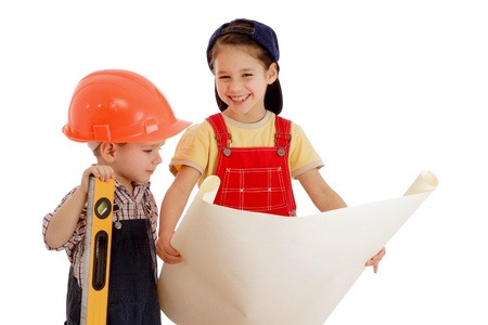 Two smiling little builders planning with liquid level and blueprint, isolated on white photo
