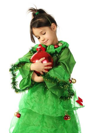 Little smiling girl in green Christmas tree costume with red Christmas decoration photo