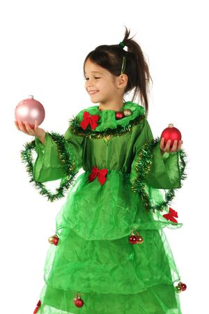 Little smiling girl in green Christmas tree costume with two Christmas decorations photo