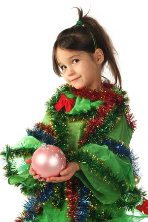 Little smiling girl in green Christmas tree costume with pink Christmas decoration photo