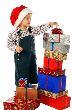 Smiling little boy with lot Christmas gift boxes photo